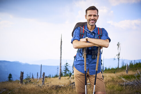 Portrait of smiling man having a break from hiking in the mountains - BSZF00689