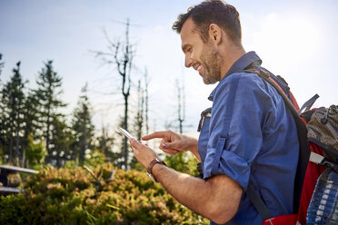 Smiling man checking his cell phone during hiking trip - BSZF00719