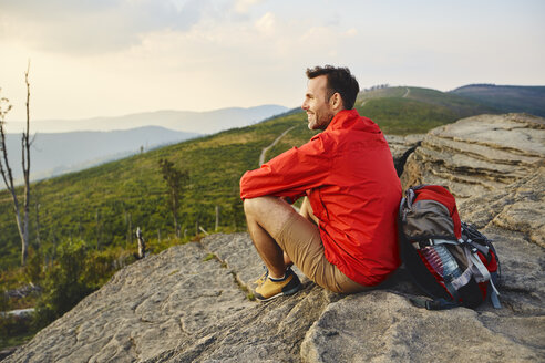Man sitting on rock enjoying the view during hiking trip - BSZF00728