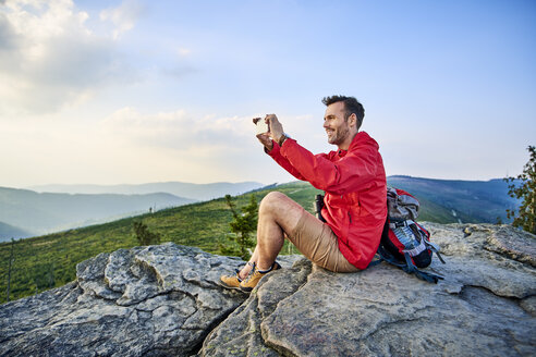 Man sitting on rock taking picture with his cell phone during hiking trip in the mountains - BSZF00731