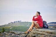 Man sitting on rock enjoying the view during hiking trip - BSZF00734