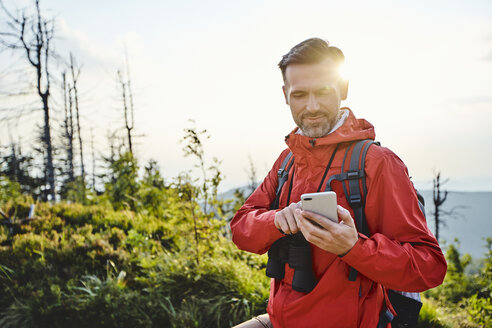 Smiling man checking his cell phone during hiking trip - BSZF00740