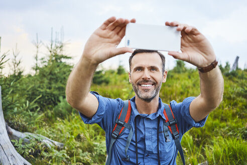 Man taking a selfie with his cell phone during hiking trip - BSZF00746