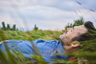 Relaxed man lying in grass - BSZF00749