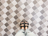 Low section of female feet on a tiled floor - INGF00140