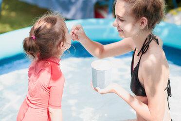 Teenage girl with her little sister enjoy eating ice cream - INGF00161