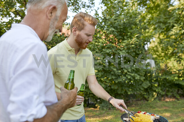 Senior father and adult son having a barbecue in garden - ZEDF01582