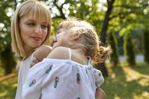 Happy mother carrying her daughter in garden - ZEDF01594