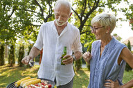 Senior couple having a barbecue in garden - ZEDF01597