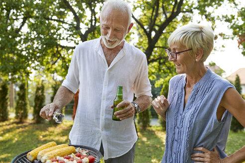 Senior couple having a barbecue in garden - ZEDF01597