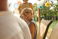 Smiling mature woman looking at husband on a garden party - ZEDF01624