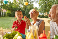 Grandmother and grandson blowing soap bubbles on a garden party - ZEDF01630