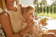 Happy mother and daughter blowing soap bubbles on porch - ZEDF01633