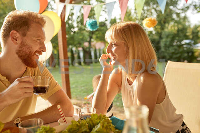 Happy couple facing each other on a garden party - ZEDF01645