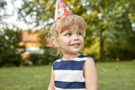 Portrait of little girl on a birthday garden party wearing party hat - ZEDF01654