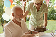 Woman handing over cake to happy husband on a garden party - ZEDF01657