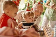 Grandfather and grandchildren blowing out candles on birthday cake on a garden party - ZEDF01672
