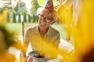 Smiling mature woman holding plate with cake on a birthday garden party - ZEDF01678
