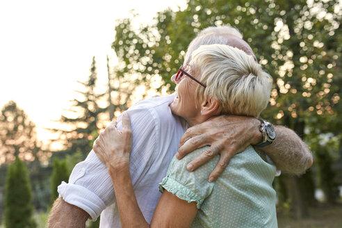 Happy senior couple hugging outdoors - ZEDF01684