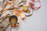High angle view of lemon and tea in a mug on a table with fairy lights - INGF00291