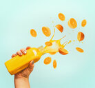 A human hand holding orange juice against a clear background - INGF00339