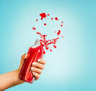 Close-up action shot of a hand squeezing red juice out of a bottle - INGF00348