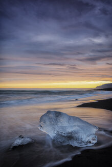 Blocks of ice form at the beach under an orange sky - INGF00369