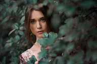 Portrait of a beautiful young woman hiding in plants - INGF00441