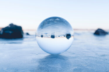 Close-up shot of a clear sphere on a snow covered landscape - INGF00447
