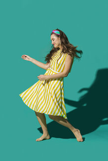 Portrait carefree young woman in striped dress dancing against turquoise background - FSIF03176