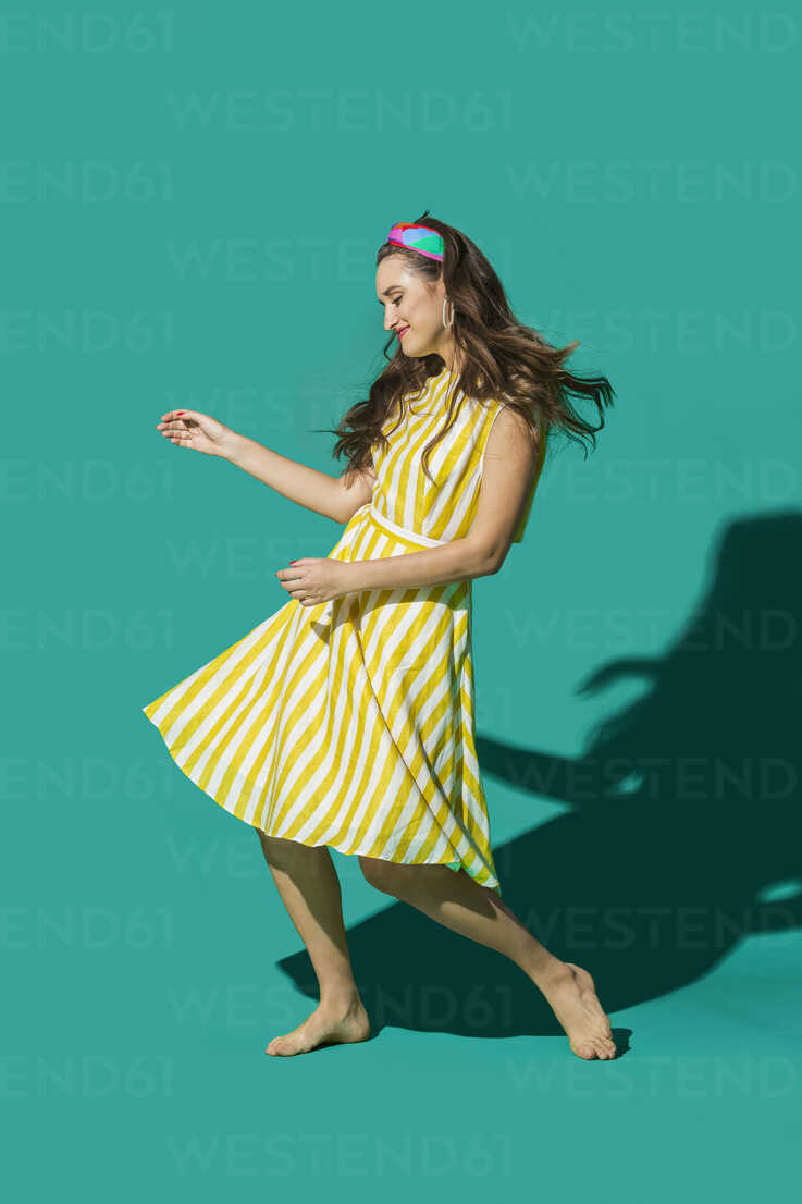 Portrait carefree young woman in striped dress dancing against turquoise background - FSIF03176 - Vladimir Godnik/Westend61