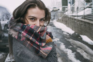 Portrait confident young woman in plaid scarf on snowy winter street - FSIF03179
