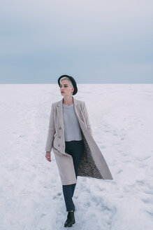 Woman in coat and hat walking in snow covered landscape - FSIF03182