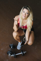 Portrait of smiling athletic woman with dumbbells, cell phone and earphones - FMGF00039