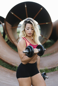 Athletic woman doing weight workout at industrial site - FMGF00045