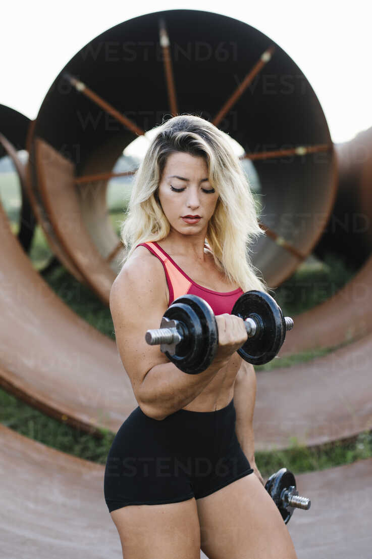 Athletic woman doing weight workout at industrial site - FMGF00045 - Nando Martinez/Westend61