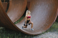 Athletic woman doing weight workout at industrial site - FMGF00048
