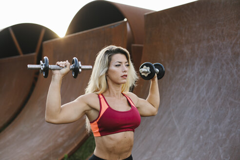Athletic woman doing weight workout at industrial site at sunset - FMGF00054