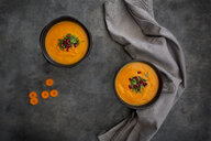 Bowl of carrot ginger coconut soup with topping of parsley and pomegranate seed - LVF07453