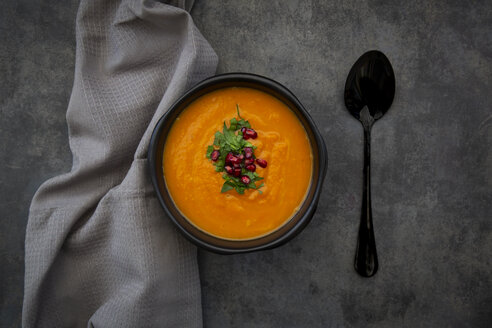 Bowl of carrot ginger coconut soup with topping of parsley and pomegranate seed - LVF07456