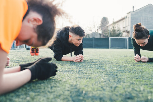 Football players in plank position on pitch - CUF45238