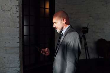 Portrait of businessman looking down at smartphone - CUF45262