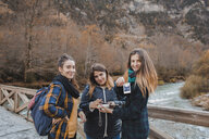 Spain, portrait of three young women with instant photos on a bridge in Ordesa National Park - AFVF01639