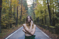 Portrait of barechested young woman standing on country road - AFVF01642