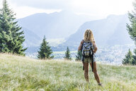 Germany, Bavaria, Oberammergau, young woman hiking standing on mountain meadow - TCF05829