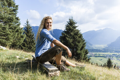 Germany, Bavaria, Oberammergau, portrait of smiling young woman sitting on bench on mountain meadow - TCF05838