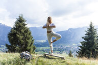 Germany, Bavaria, Oberammergau, young woman doing yoga on bench on mountain meadow - TCF05844