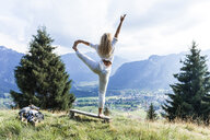 Germany, Bavaria, Oberammergau, young woman doing yoga on bench on mountain meadow - TCF05847