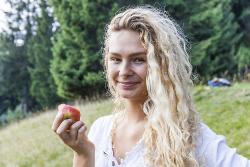 Germany, Bavaria, Oberammergau, portrait of smiling young woman eating an apple on mountain meadow - TCF05850
