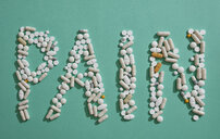Painkiller pills spelling out Pain on green background - FSIF03205
